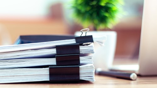 Stack of tender documents on a desk