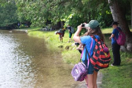 children standing along the park shoreline taking pictures